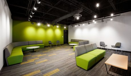Industrial Lounge – Floor design – Carpet tile installation – Exposed ceiling – Upholstered office benches – Bright green painted wall – Spotlights
